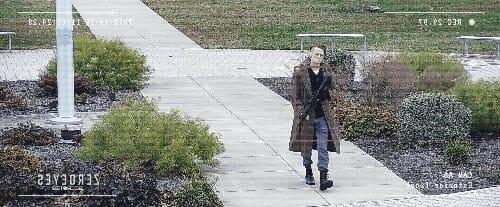 armed assailant walking toward building